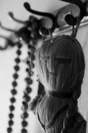 A doll made of hey threads and a necklace made of  wooden beads used by old age person to chant the name of god  Symbolizes belonging and togetherness among the two generations