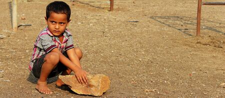 Marathwada region of Maharashtra,India has been severely hit by a draught. This Image is of a Child playing in the dry park with the stone.