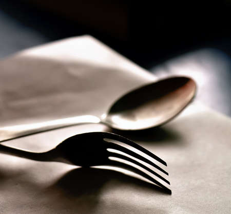 Spoon and fork kept on a white base photo