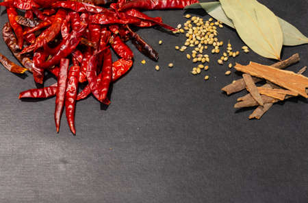 Colorful Spices and herbs with vegetables frame on a black wooden background.