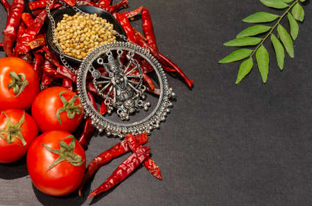 Colorful Spices and herbs with vegetables frame on a black wooden background