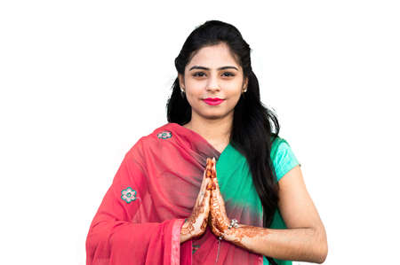 Young pretty asian or Indian woman doing namaste and greeting at camera.