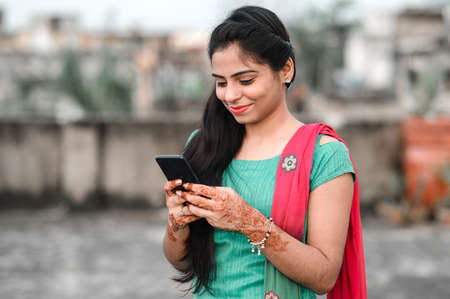 Pretty young Indian woman using her phone. Stock Photo