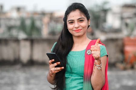 Pretty young Indian woman using her phone and showing thumbs up sign.