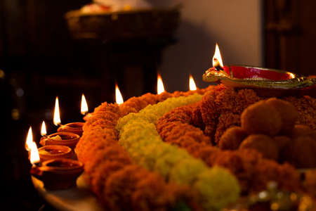 Diwali glowing Diya , flowers, Sweets and Gifts arranged in circular shape forming a design with copy space, selective focus , Indian festival Stock Photo
