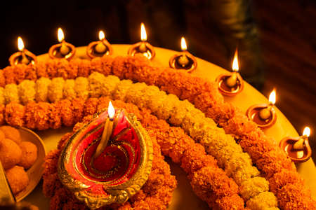 Diwali glowing Diya , flowers, Sweets and Gifts arranged in circular shape forming a design with copy space, selective focus , Indian festival