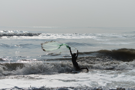 Fishermans throw against upcoming waves