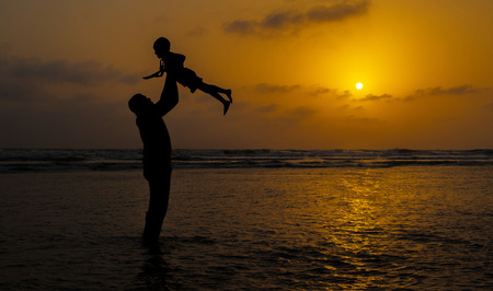 Father and child playing on the beach during sunset