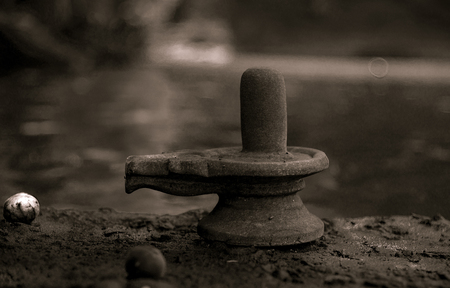 An old shiva linga on a river bank
