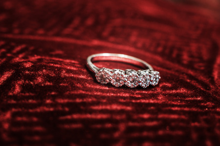 A macro shot of a diamond ring on a red velvet cloth. Stock Photo