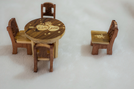 Wooden Miniature table and chairs in a white background