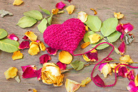 purple knitted valentine s heart with rose petals on a wooden background  photo
