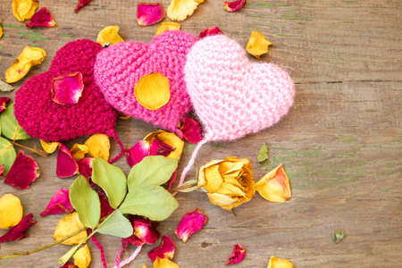 knitted hearts on a wooden background with rose petals  photo