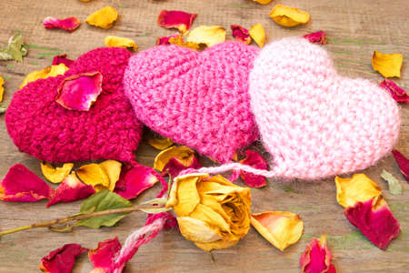 three knitted hearts on a wooden background  photo
