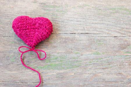 bondad: corazón púrpura de punto en una textura de madera vieja agrietada Foto de archivo