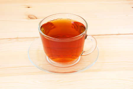 invigorate: cup of fragrant tea on a wooden background