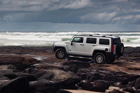 Ein 4wd Hummer, der an einem stürmischen Tag über Felsen an einem felsigen Strand fährt