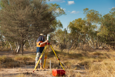 Surveyor with EDM Leica theodolite working in extreme conditions in the Australian outback