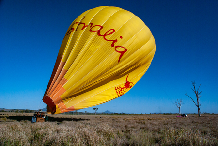 Hot air balloon landing in a large field