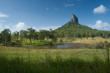 Rolling fields and lake dominated by Mt Coonowrin one of the Glasshouse Mountains