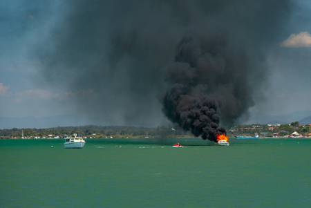 A small boat on fire with other boats to the rescue