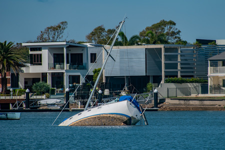 The remnants of a tropical storm left a few yachts and boats in trouble in Molloolaba. Here a yacht has partially sunk in the high winds