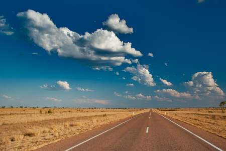 A long empty road in the Australian outback with a blue sky and white fluffy clouds.