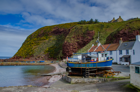 A blue fishing boat sits out of the water in Pennan, a small village in northern Scotland