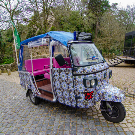 A colorfully decorated tuk tuk is used in Portugal for transporting tourists to and from attractions