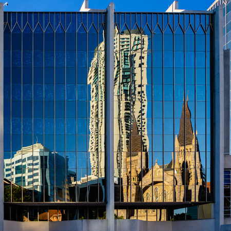 St Stepehens Cathedral and surrounding buildings are seen here reflected in a Brisbane CDB building