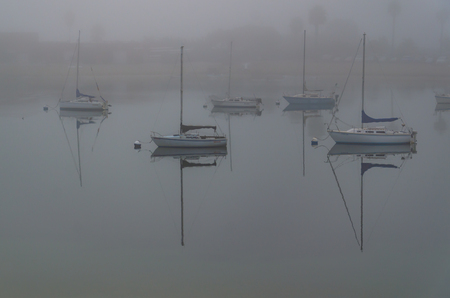 A misty morning just after sunrise in San Diego. Here yachts sit moored in the calm waters of the lake
