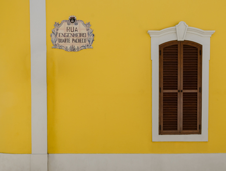 A nice street sign,clean yellow walls and a window with wooden shutters in this minimalist view - Loule, Portugal Stock fotó