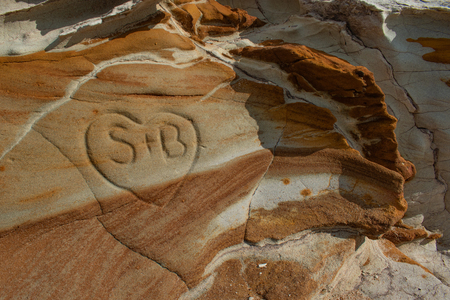 A heart carved into a limestone rock outcrop with different bands of rock, color and patterns Stock Photo