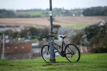 A bicycle leaning against a lamp post on a hill in St Andrews in Scotland