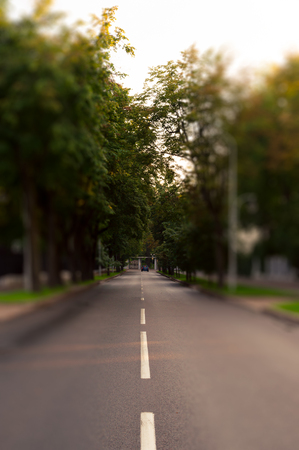 Quite city street in tilt shift technique. Alone car far side. Natural evening light