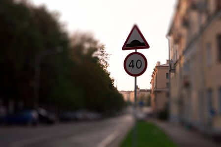 city limit: Traffic sign with speed limit on quite city street at sunset. Blur mode all besides sign