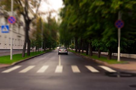 urban road: Car and cross walk of quite city street. Tilt shift technique. Natural evening light and green grass.