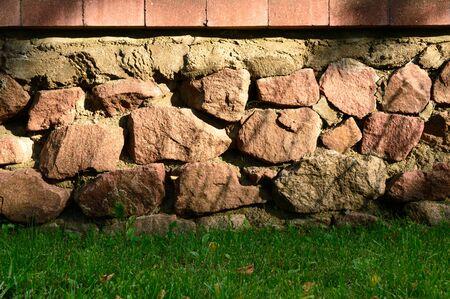 weed block: Brick and stone wall closeup with green weed below