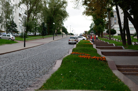 quite: Quite city street with people going around. Green grass in middle and paving stone road