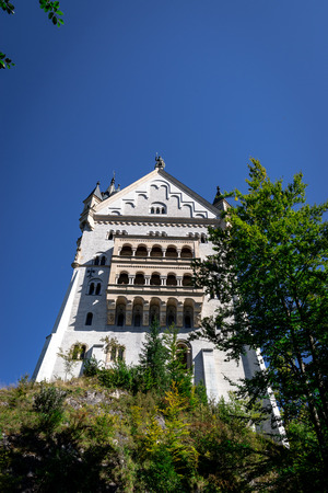 Neuschwanstein castle in Germany. Castle and mountains with trees around Editorial