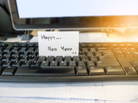 Happy new year white card placed at the computer board Stock Photo