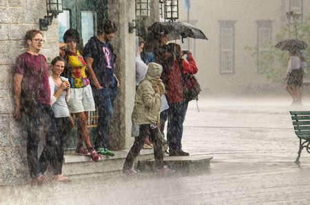 sotto la pioggia: Quebec City, Canada - 27 Luglio, 2014: Un gruppo di persone nascondere dalla pioggia battente sotto un edificio.