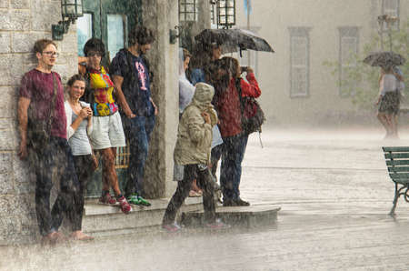 soaked: Quebec City, Canada - July 27, 2014: A group of people hide from heavy rain under a building. Editorial
