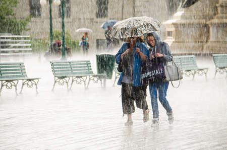 raining: Quebec, Canadá - 27 de julio 2014: Un grupo de personas se esconden de la lluvia pesada bajo un edificio. Editorial