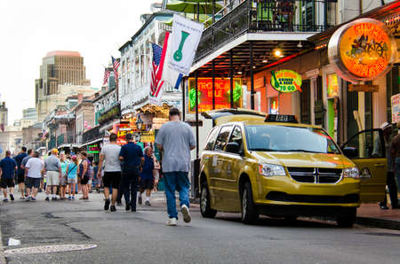 bourbon street: New Orleans, USA - July 8, 2015: A crowd of people walk in the evening on famous Bourbon Street in New Orleans, Louisiana.