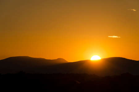 basin mountain: A colorful sunset in Santa Fe, New Mexico with a sun hiding behind mountains.