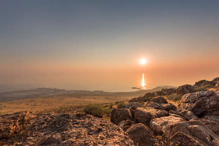 basin mountain: Sunset and ray path at the top of Antelope Island with rocks at the foreground located near Salt Lake City, Utah. Stock Photo
