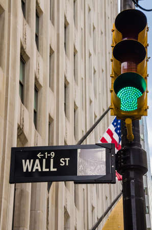 financial market: Wall street sign with green traffic light taken in New York City