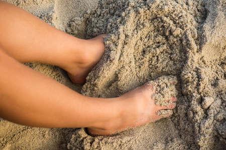 dirty feet: A tan womans legs in wet sand