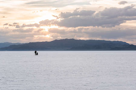 vast: Two people in the distance in the vast salt flats near Salt Lake City, Utah during sunset